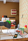 Retro cleaning utensils on woven rug and Tulip table with black and white polka-dot tablecloth; wall in 70s-style brown