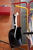Brush with animal-shaped handle and black dustpan hanging from colourful, retro coat rack