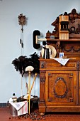 Various cleaning utensils next to antique dresser and cuckoo clock on wall