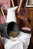 Retro enamel jug, metal buckets and brushes on antique armchair