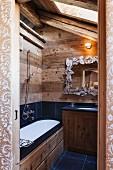 Holz und anthrazitfarbene Fliesen in rustikalem Badezimmer unterm Dach; Spiegel mit künstlerisch gestaltetem Rahmen