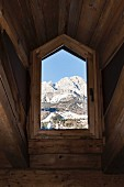 View of Dolomite Mountains through rustic dormer window of chalet