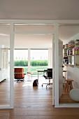 Arbeitszimmer mit Möbelklassikern und Gartenblick, im Vordergrund Glastrennwand mit weiss lackiertem Holzrahmen