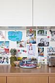 Küchenunterschrank aus Holz und weisser Hängeschrank, dazwischen Magnetwand mit Fotosammlung