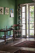 Hostess trolley used as telephone table in room with green walls and open French windows leading to garden