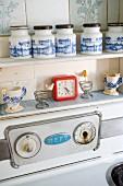 Nostalgische Gewürzdosen, Eierbecher und Uhr über Herd in Küche