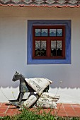 Vintage rocking horse and cushions with vintage-style lettering outside farmhouse with blue border around window