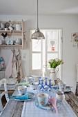 Pendelleuchte über gedecktem Esstisch in nostalgischer Shabby Wohnküche