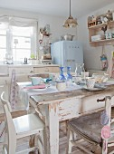 Dining table and chairs in vintage-style shabby-chic kitchen-dining room with pale blue fridge in background