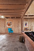 Turquoise armchair in renovated, wood-clad interior