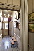 Narrow hallway with white-painted wooden floor, gallery of pictures and pale curtain in foreground