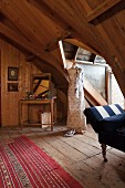Wood-clad attic room with tailors' dummy wearing long summer dress in dormer
