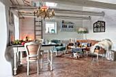 Eklektizismus im rustikalen Landhaus, weiße Stühle an Esstisch, im Hintergrund Lounge mit Rokoko Sitzmöbel