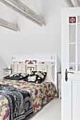 Doppelbett mit floral gemusterter Tagesdecke und kunsthandwerklichem hölzernem Bettkopfteil in Schlafzimmer