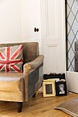 Union flag cushion on old leather armchair next to picture frame leaning against door frame