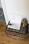 Aufgeschlagenes Buch mit Gedicht und Aktzeichnung auf Schallplattensammlung in alter Holzkiste