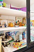 Children's books and toys in glass-fronted cupboard