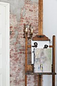 Painting on old easel in front of antique sconce lamp on unrendered brick wall