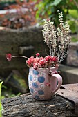 Succulents and thyme planted in mug with retro pattern