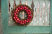 Wreath of bark and small red apples hung on weathered wooden door