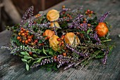 Wreath of physalis, heather and sprigs of berries on wooden surface