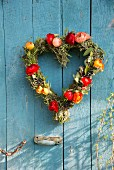 Heart-shaped wreath of multicoloured ranunculus on blue-painted wooden wall