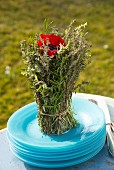 Posy of herbs with red anemone in centre on stack of pale blue plates outdoors
