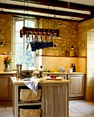 Solid wood island counter with cabinets below pans hanging from rack in rustic kitchen