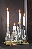 Weihnachtlich dekorierte Glasflaschen mit Kerzen als Adventskranz