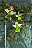Paper angels with heads cut out of family photos hung on fir branch