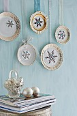 Decorative plates embellished with snowflake motifs hung from ribbons on pastel-blue wall
