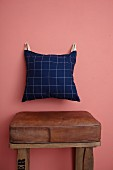Hand-sewn cushion hung on wall from leather straps