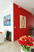 Rot-orangefarbener Tulpenstrauss vor männlicher Aktzeichnung an rot getönter Wand in modernem Ambiente