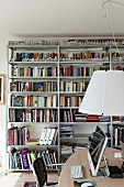 Desk below pendant lamp with white lampshade and metal bookshelves in background