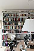 Arbeitstisch unter Pendelleuchte mit weißem Lampenschirm, an Wand Metallregale mit Büchern