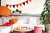 Comfortable corner bench with white cover, orange Balinese parasol and bunting