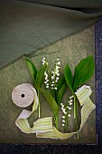 Lily-of-the-valley flowers and leaves and fabric ribbon lying on paper