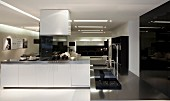 Free-standing kitchen counter with white base cabinets and hob; recessed lighting strips in ceiling