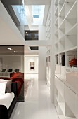 Open-plan, contemporary, showroom house with bedroom area and white shelving with many compartments