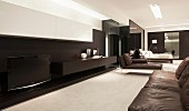 Open-plan lounge with black floating sideboard, white wall-mounted cabinet and modern chaise with black leather upholstery