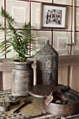 Sprigs of fern in vintage vase and bottle on table in rustic interior
