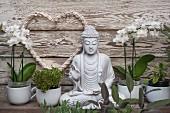 Kräutertöpfe und weisse Orchideen neben Buddhafigur vor Holzwand mit aufgehängter Herzform
