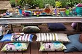 Niedriger Gartentisch, in asiatischem Stil, mit farbigen Gläsern und Blumendeko, Sitzkissen auf Holz Terrassenboden