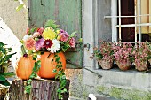 Bouquet in hollowed-out pumpkin used as vase on tree stump outside rustic house
