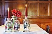 Alte Glasflaschen, mit Weihnachtsmotiven beklebt, als Kerzenhalter