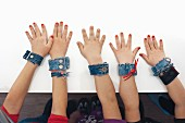 Arms of children wearing denim bracelets