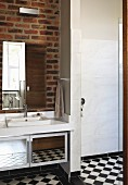 Washstand and mirrored cabinet on exposed brick wall and chequered floor in bathroom
