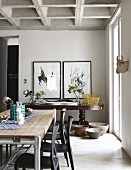 Contemporary table, dark chairs and antique console table in dining room with concrete coffered ceiling