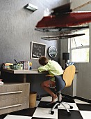 Boy sitting on swivel chair at desk in bedroom with chequered tiled floor