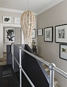 Designer pendant lamp and gallery of artworks in stairwell with metal landing balustrade and black, masonry stair balustrade